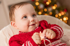 Christmas time. Cute baby plays with the lights decorations, Stock Images