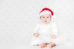 Christmas time. Cute baby sitting wearing cute Santa hat and white dress. Royalty Free Stock Photography