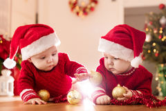 Christmas time. Cute baby twin sisters play with glass balls. Royalty Free Stock Images