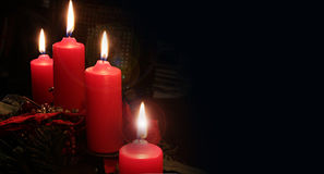 Christmas time, four candles lit on black background Royalty Free Stock Photos