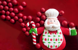 Christmas time – funny toy Santa Claus with red balls in the background Stock Photography