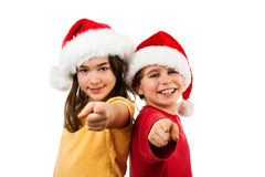 Christmas time - girl and boy with Santa Claus Hat pointing. Christmas time - kids with Santa Claus hat on white background Stock Image