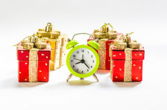 Christmas time. Green alarm clock between present shaped Christmas decorations Royalty Free Stock Images