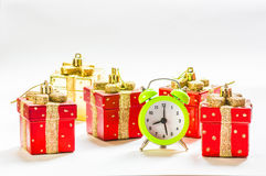 Christmas time. Green alarm clock between present shaped Christmas decorations Royalty Free Stock Photos