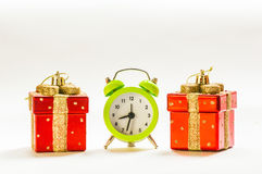 Christmas time. Green alarm clock between two present shaped Christmas decorations Stock Images