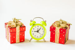 Christmas time. Green alarm clock between two present shaped Christmas decorations Royalty Free Stock Photography