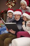 Christmas time for happy family. Children love when their father reads them Royalty Free Stock Images