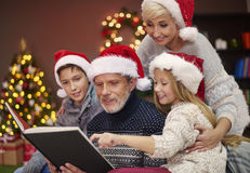 Christmas time for happy family. Reading in that atmosphere is a pure pleasure Royalty Free Stock Photo