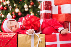 Christmas time, little baby child sleeping and holding gift Stock Photo