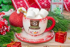 Christmas time. A mug with a snowman, marshmallow and gingerbread cookies on a wooden table is decorated with Christmas decoration. S, fir branches, toys with a stock image