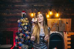 Christmas time. New years eve girl. Winter eve night emotion reactions. Sparkles party, Bengal lights. Christmas tree. Decorate at home. Happy new year royalty free stock image