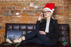Christmas time in office. Young beautiful blond business woman on leather couch. Business concept. Christmas time in office. Young beautiful blond business Royalty Free Stock Photos