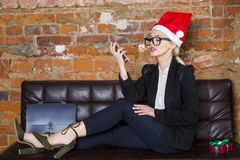 Christmas time in office. Young beautiful blond business woman on leather couch. Business concept. Christmas time in office. Young beautiful blond business Stock Photo
