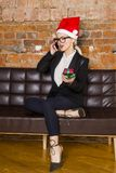 Christmas time in office. Young beautiful blond business woman on leather couch. Business concept. Christmas time in office. Young beautiful blond business Stock Image