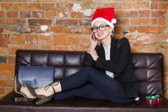 Christmas time in office. Young beautiful blond business woman on leather couch. Business concept. Christmas time in office. Young beautiful blond business Royalty Free Stock Photo