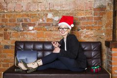 Christmas time in office. Young beautiful blond business woman on leather couch. Business concept. Christmas time in office. Young beautiful blond business Royalty Free Stock Images