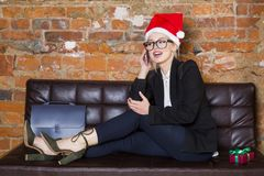 Christmas time in office. Young beautiful blond business woman on leather couch. Business concept. Christmas time in office. Young beautiful blond business Stock Images
