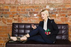 Christmas time in office. Young beautiful blond business woman on leather couch. Business concept. Christmas time in office. Young beautiful blond business Royalty Free Stock Photography