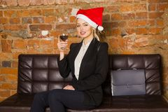 Christmas time in office. Young beautiful blond business woman on leather couch. Business concept. Christmas time in office. Young beautiful blond business Stock Photos