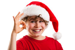 Christmas time - OK sign. Christmas time - boy with Santa Claus hat isolated on white background Stock Photos