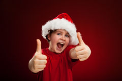 Christmas time - OK sign. Christmas time - boy with Santa Claus hat on red background Stock Photo