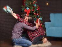 A lovely couple gives each other presents for Christmas. pleasant emotions Stock Photos