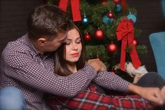 A loving couple gently hugs near a Christmas tree on New Year`s Eve royalty free stock photos