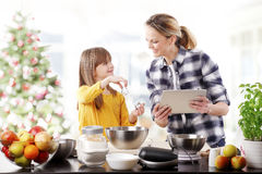 Christmas time. Portrait of happy mother and her cute daughter baking together at home in christmas time Stock Photos
