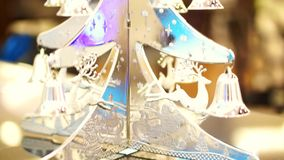 Christmas time silver ornament, reindeer and bell hanging on a tree stock footage