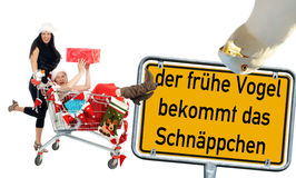 Christmas time. Two women at the christmas shopping and sign with the german words the early bird gets the bargains Royalty Free Stock Photography