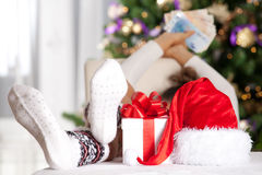 Christmas time. Woman relaxing with legs on the table, holding money in the hand in front of a christmas tree. Christmas background. Christmas, shopping and Stock Images