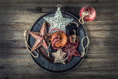 Christmas time. Wrought metal plate filled with various Christmas decorations. Christmas stars, Jingle bells in various positions. Stock Photo
