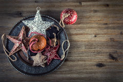 Christmas time. Wrought metal plate filled with various Christmas decorations. Christmas stars, Jingle bells in various positions. Royalty Free Stock Photography
