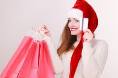 Woman in Christmas hat holds credit card and shopping bags. Royalty Free Stock Photography