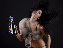 Christmas time. Young woman in studio with bottle champagne, isolated grey background Stock Image