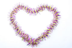 Christmas tinsel. Pink and yellow Christmas tinsel on a white Royalty Free Stock Images