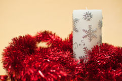 Christmas tinsel with candle decoration. Isolated on yellow background Royalty Free Stock Photo