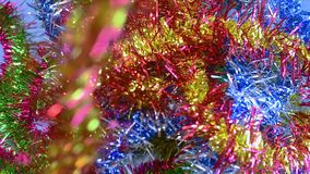 Christmas tinsel, frippery falls on the table. New year, Christmas, holidays. Christmas background, tinsel, frippery. The light is reflected in the tinsel stock video footage