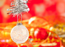 Christmas tinsel snow crystal bauble on red. Christmas card tinsel snow crystal bauble on red blurred background Stock Image