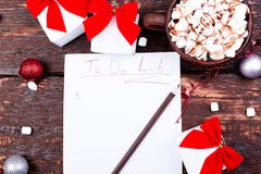 Christmas To Do List. Cup of hot cocoa or chocolate with marshmallow on wooden background. Flat lay. Christmas planning concept. Royalty Free Stock Photography