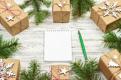 Christmas to-do list or wish list. Christmas background with blank notebook, fir branches, decorations and gift boxes. Copy space. Top view Stock Image