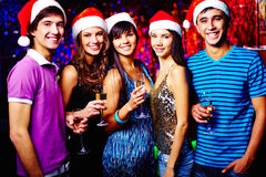 Christmas toast. Group of joyful friends in Santa caps toasting at party stock photography