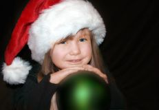 Christmas Toddler. Picture of beautiful little girl wearing a christmas hat and holding a green christmas ball decoration, against a black background Royalty Free Stock Images