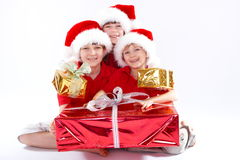 Christmas Togetherness. Three kids with Christmas gifts Stock Photo