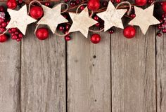 Christmas top border with rustic wood star ornaments and baubles over aged wood Stock Photo