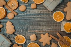 Christmas top view over a brown wooden background with gift boxes packed in a craft paper with dryed oranges, cookies. And christmas decorations. Flat lay, copy royalty free stock images