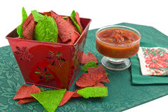 Christmas tortilla chips and salsa. Red and green tortilla chips in christmas theme container with black bean and corn salsa on green mat Stock Photography