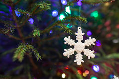 Christmas toy as a snowflake. Hanging on a Christmas tree stock photo