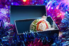 Christmas toy in  the box on the background of Christmas tinsel Royalty Free Stock Photo