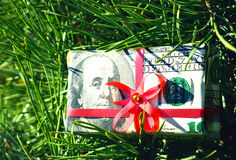 Christmas toy box with a red bow made of dollar bills on the branch of spruce Royalty Free Stock Images